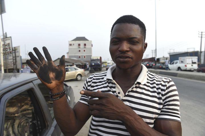 Un homme essuie sa voiture avec sa main pour montrer combien la suie en a recouvert le capot, dans la ville de Port Harcourt, le 14 février 2017. La suie est tombée du ciel provocant la colère des résidents qui affirment que rien n'est fait pour protéger leur santé. (PIUS UTOMI EKPEI/AFP)