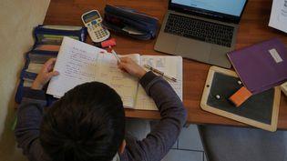 Un enfant fait ses devoirs à la maison. Illustration. (GUILLAUME SOUVANT / AFP)
