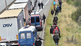 Des policiers aux côtés de migrants sur la route qui conduit au port de Calais (Pas-de-Calais), le 5 août 2015. (PHILIPPE HUGUEN / AFP)