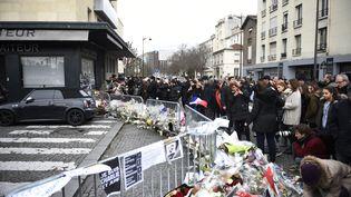 Des dizaines de personnes rendent hommage aux victimes de la prise d'otages dans l'épicerie cacher de la porte de Vincennes, à Paris,le 12 janvier 2015. (MARTIN BUREAU / AFP)