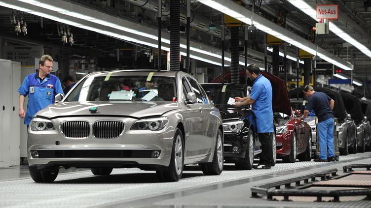 Des ouvriers travaillent sur une chaîne d'assemblage du constructeur allemand BMW dans son usine de Dingolfing, dans le sud de l'Allemagne, le 23 mars 2012. (CHRISTOF STACHE / AFP)