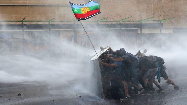 Des manifestants qui tiennent un drapeau Mapuche alors qu'ils sont repoussés par un canon d'eau à Santiago (Chili), le 20 novembre 2019. (PABLO SANHUEZA / REUTERS)