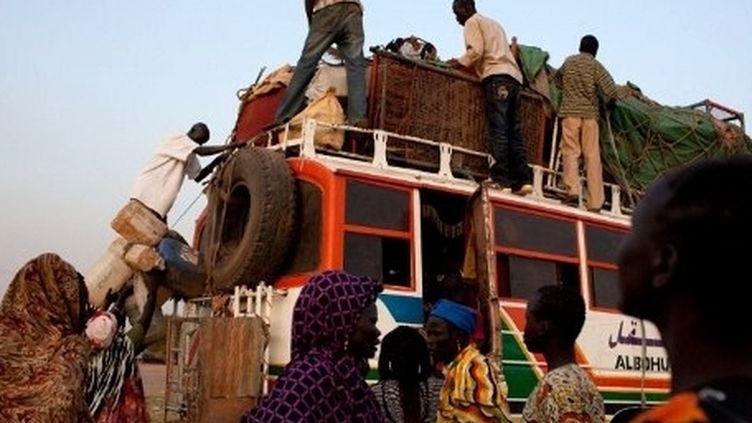 Des Soudanais se préparent à emprunter le long voyage vers l'exile. (YASUYOSHI CHIBA / AFP)