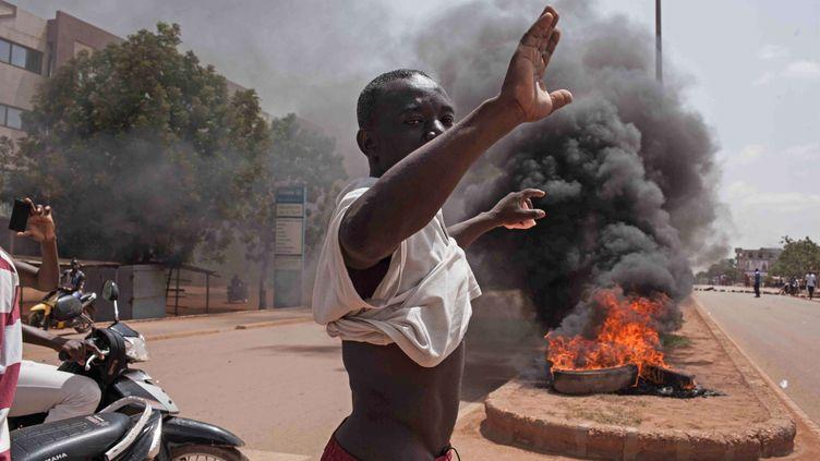 Un manifestant devant des pneus brûlés dans les rues de la ville de Ouagadougou, au Burkina Faso, le 17 septembre, 201 (THEO RENAUT / AP / SIPA )