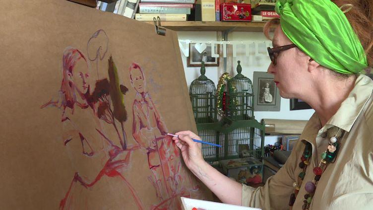 """Nathalie Novi, l'initiatrice du projet de fresque collective, en train de peindre sa """"famille confinée"""",dans son atelier du Jura. (H. Perret / France Télévisions)"""