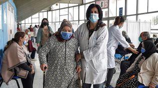 Uneinfirmièreaccompagneune femme âgée pour recevoir une dose du vaccin contre le coronavirus à la salle de sport El-Menzah à Tunis, le 12 avril 2021. (FETHI BELAID / AFP)