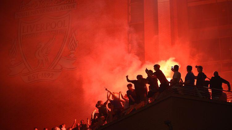 Des supporters de Liverpool fête le tire de leur club, le 26 juin 2020. (OLI SCARFF / AFP)
