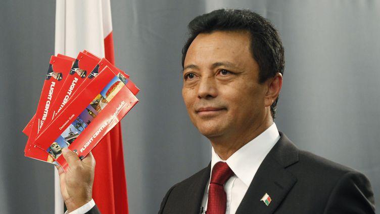L'ancien président malgache Marc Ravalomanana brandit ses billets d'avion qui l'emmèneront à Madagascar le 21 janvier 2012. (MIKE HUTCHINGS / REUTERS)