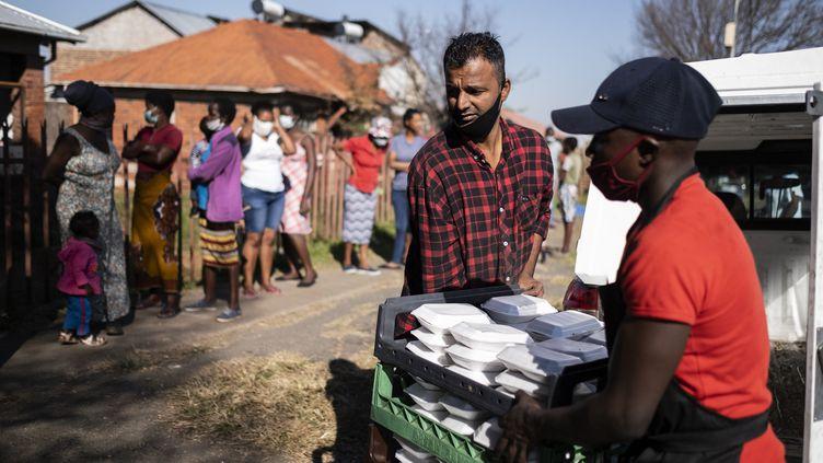 Des bénévoles distribuent de lanourriture dans un quartier de Johannesburg (Afrique du Sud) le 12 mai 2020, pendant le confinement lié à l'épidémie de coronavirus. (WIKUS DE WET / AFP)