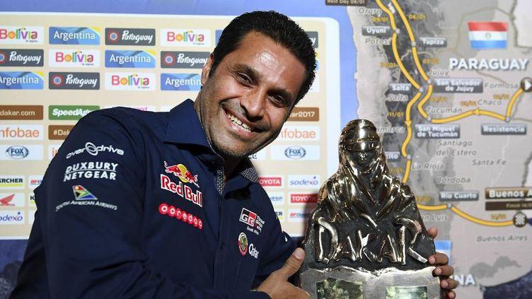Le Qatari Nasser al-Attiyah prend la pose avec un trophée lors de la conférence de presse de présentation de l'édition2017, le 23 novembre 2016 à Paris. (FRANCK FIFE / AFP)