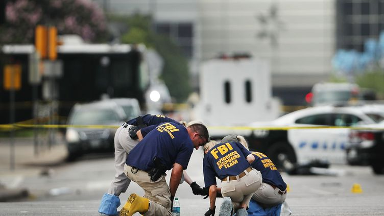 Des membres du FBI récoltent des preuves sur les lieux où cinq policiers ont été abattus moins de 48 heures plus tôt, samedi 9 juillet 2016 à Dallas (Texas). (SPENCER PLATT / GETTY IMAGES NORTH AMERICA / AFP)
