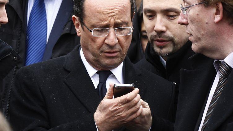 François Hollande consulte son téléphone portable, le 27 avril 2012, lors d'une visite au festival du Printemps deBourges (Cher). (JACKY NAEGELEN / REUTERS)