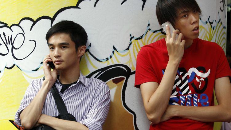 Deux hommes téléphonent à Hong Kong le 16 août 2011. (BOBBY YIP/REUTERS)