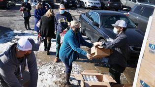 Des habitants reçoivent de l'eau lors d'une vague de froid polaire à Austin au Texas, le 19 février 2021. (JOE RAEDLE / GETTY IMAGES NORTH AMERICA / AFP)