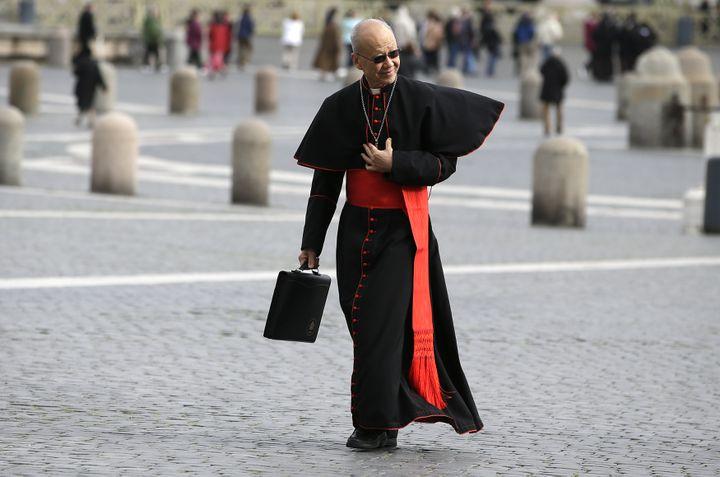 Le cardinal chinois John Tong Hona agrémenté sa soutane noire ajustée d'une touche de modernité avec des lunettes de soleil à fines branches et une serviette en cuir.Au Vatican, le 8 mars 2013. (MAX ROSSI / REUTERS)
