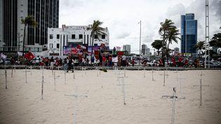 Plusieurs croix sont placées sur la plage àRecife au Brésil, samedi 23 janvier 2021, lors d'une manifestation contre le gouvernement Bolsonaro. (PAULO PAIVA / AGIF / AFP)