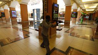 Un policier kényan armé à la recherche des hommes armés et masqués qui ont ouvert le feu samedi 21 septembre 2013 sur les clients et le personnel d'un centre commercial de luxe à Nairobi (Kenya). (GORAN TOMASEVIC / REUTERS)
