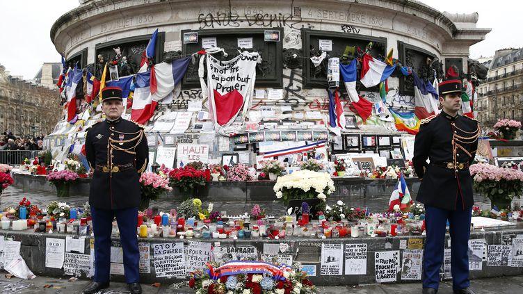Des gardes républicains se tiennent devant la statue de la République, le 10 janvier 2016, à Paris, où des fleurs et des bougies ont été déposées en mémoire des victimes des attentats de novembre 2015. (YOAN VALAT / AFP)