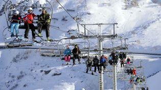 Des skieurs prennent un télésiège dans les Alpes françaises, en février 2014 (image d'illustration) (Illustration/PHILIPPE DESMAZES / AFP)
