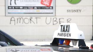 """Un graffiti """"A mort Uber"""" s'affiche derrière les conducteurs de taxi porte Maillot à Paris, le 25 juin 2015. (CITIZENSIDE / ANTHONY DEPERRAZ / CITIZENSIDE.COM)"""