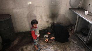 Une femme syrienne cuisine de la poudre de riz dans sa cuisine à Douma, une ville de la Ghouta orientale, en novembre 2017. (HAMZA AL-AJWEH / AFP)