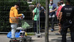 Une personne offrant des provisions à des employés de l'abattoir Toennies qui doivent rester à leur domicile, en Rhénanie-du-Nord-Westphalie, (Allemagne), le 22 juin 2020. (INA FASSBENDER / AFP)