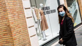 Des clients patientent dans la rue avant d'entrer dans des magasins, pour respecter les consignes sanitaires, dans le centre ville de Toulouse, le 16 mai 2020. (MATTHIEU RONDEL / HANS LUCAS / AFP)