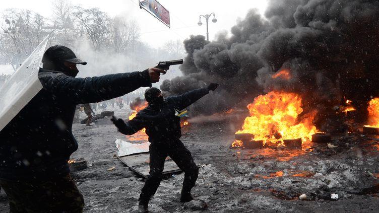 Des manifestants, armes au poing, tirent sur les forces de l'ordre ukrainiennes dans le centre de Kiev (Ukraine), le 22 janvier 2014. (VASILY MAXIMOV / AFP)
