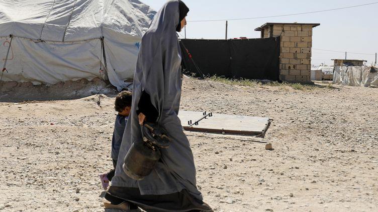 Une mère marche avec son enfant dans un camp du groupe Etat islamique dans le villageAl-Malikiyah en Syrie, le 29 septembre 2018. (DELIL SOULEIMAN / AFP)