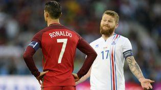 Le Portugais Cristiano Ronaldo et l'Islandais Aron Gunnarsson, le 14 juin 2016 à Saint-Etienne (Loire). (EPA / MAXPPP)