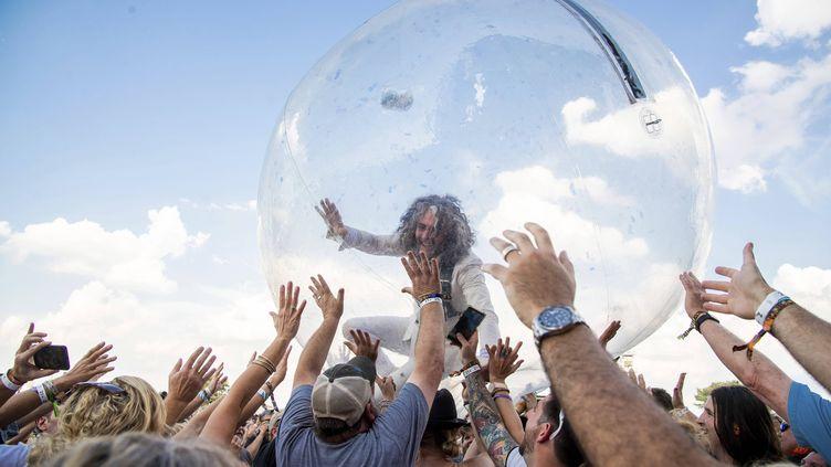 Wayne Coyne, le chanteur du groupe Flaming Lips, surfe sur le public dans une bulle, le 20 septembre 2019, à Louisville (Kentucky, Etats-Unis). (AMY HARRIS / AP / SIPA)