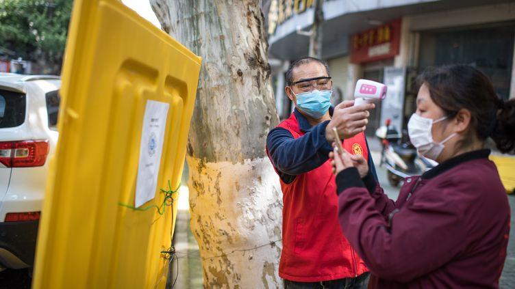 """Un membre de """"l'équipe d'urgence de Wuhan"""" prend la température d'une habitante à Wuhan (Chine), le 25 avril 2020. (MAXPPP)"""
