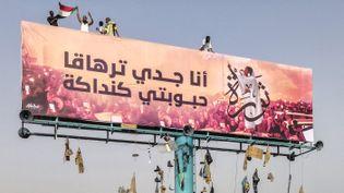 """Immense affiche de rue montrant une image d'Alaa Salah, qualifiée de """"kandaka"""" (souveraine antique) et devenue une icône des réseaux sociaux mondiaux. L'inscription en arabe signifiant : """"Mon grand-père est Taharka (pharaon koushite au VIe avant notre ère, NDLR),mon aimée est Kadaka"""". (- / AFP)"""