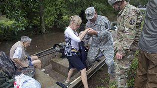 Plus de 7000 personnes ont été secourues en Louisiane (Etats-Unis) depuis le début des inondations, vendredi 12 août 2016. Cette femme a dû emprunter une barque pour être amenée en lieu sûr, dimanche. (MAX BECHERER / AP / SIPA)