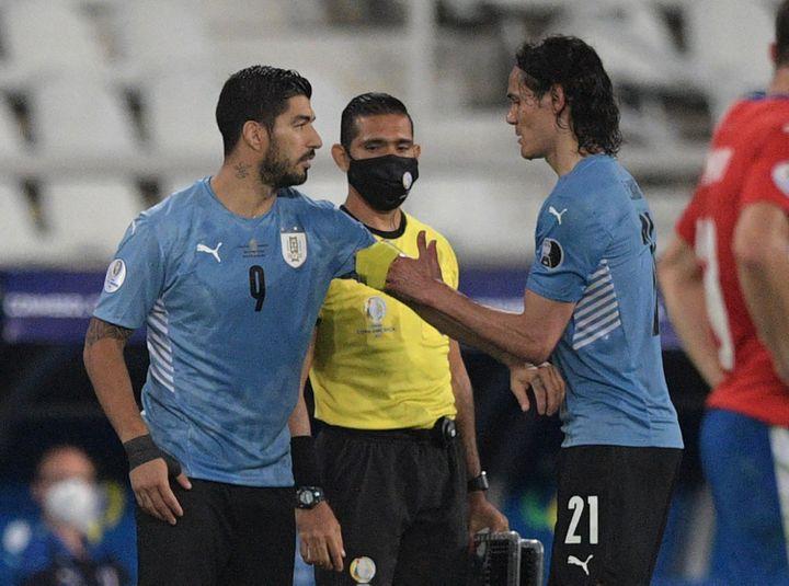 Edinson Cavani donne le bracelet de capitaine à son remplaçant, Luis Suarez, lors de la rencontre de phases de poule face au Paraguay le 28 juin dernier. (CARL DE SOUZA / AFP)