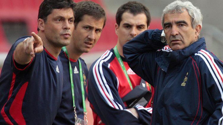 L'entraîneur français Raymond Domenech (à droite) écoute l'entraîneur du gardien de but Bruno Martini (à gauche) lors d'une séance d'entraînement au stade de Cologne à la veille du match France-Togo de la Coupe du monde de football 2006, le 22 juin.   (PASCAL PAVANI / AFP)
