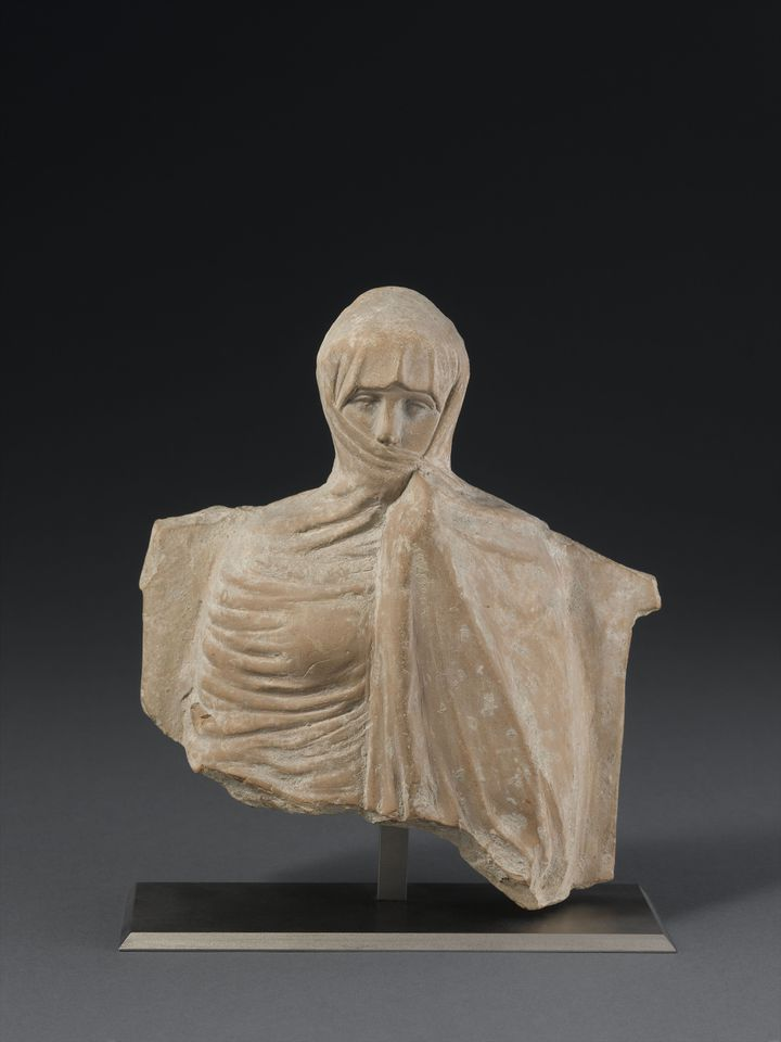 Chypre, Femme voilée, vers 450 av. J.-C., terre cuite, Paris, musée du Louvre, département des Antiquités grecques, étrusques et romaines.Découverte à Chypre, cette figurine témoigne de l'apparence des vêtements l'époque hellénistique (IVe siècle – 31 av. notre ère), aujourd'hui disparus en raison de leur fragilité. La jeune femme est vêtue d'un manteau appelé himation, ramené en voile sur sa tête. (RMN Grand Palais - Franck Raux)