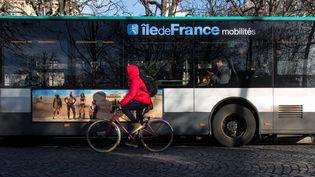 Un cycliste circule près d'un bus, le 10 décembre 2019, à Paris. (RICCARDO MILANI / HANS LUCAS / AFP)