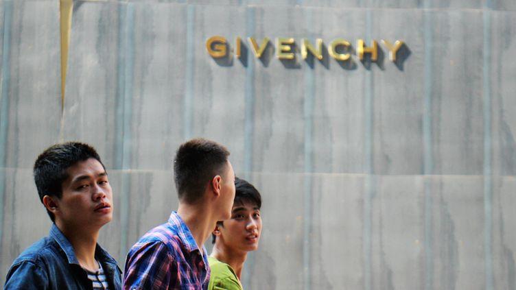 Des habitants marchent devant la boutique Givenchy à Chongqing, en Chine, en 2015. (HE LILI / IMAGINECHINA)