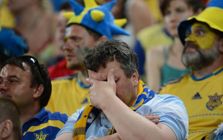 Un supporter ukrainien, effondré, après la défaite de son pays contre la France, le 15 juin 2012. (FRANCK FIFE / AFP)