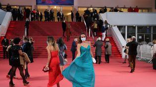 Des invités masqués arrivent au Palais des festivals à Cannes pour une mini-cérémonie confinée le 7 octobre 2020. (VALERY HACHE / AFP)