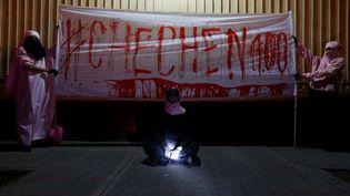 Lesmilitants du groupe d'artistes mexicains D3 Chok3 déploient une banière ensanglantée devant l'embassade de Russie à Mexico (Mexique), jeudi 20 avril 2017, pour dénoncer les violences commises contre les homosexuels en Tchéchénie. (CARLOS JASSO / REUTERS)