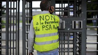 Un employé du site PSA d'Aulnay-sous-Bois manifeste contre l'annonce de la fermeture de l'usine en 2014, le 12 juillet 2012. (YOAN VALAT / MAXPPP)