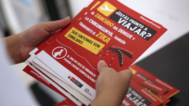 Un employé du ministère de la Santé du Pérou distribue des prospectus pour prévenir du virus Zika, le 4 février 2016, à Lima (Pérou). (MARIANA BAZO / REUTERS)