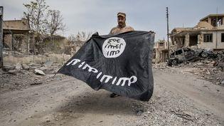 Un drapeau du groupe Etat islamique, exhibé dans les ruines de Mossoul (Irak) par un soldat irakien, le 7 juillet 2017. (SEBASTIAN BACKHAUS / NURPHOTO / AFP)