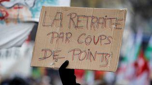 """Une pancarte """"La retraite par coups de points"""" tenue par un manifestant, le 5 décembre 2019 à Paris. (THOMAS SAMSON / AFP)"""