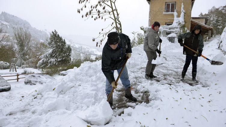 Des habitants de Valfleury, près de Saint-Etienne (Loire), dégagent la neige accumuléedevant leur maison, le 20 novembre 2013. (PHILIPPE DESMAZES / AFP)