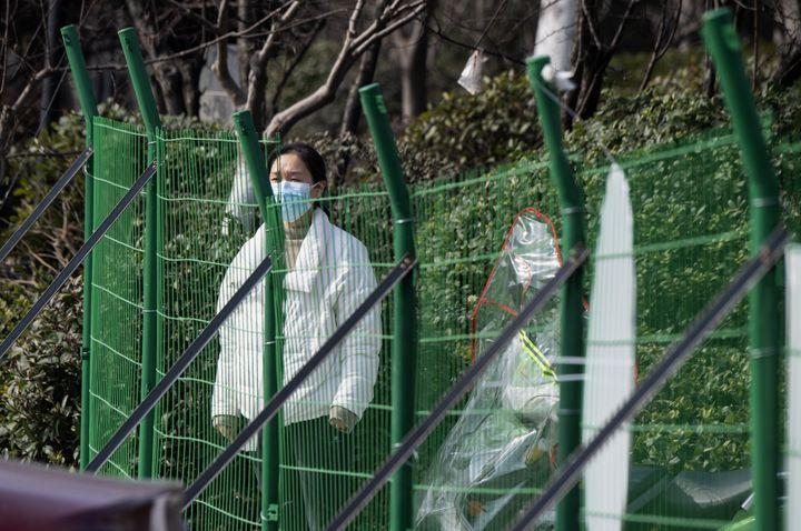 Une résidente porte un masque derrière une barrière installée le long d'une rue de Hangzhou (Chine) située près du siège du groupe Alibaba, le 5 février 2020. (NOEL CELIS / AFP)