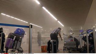 Sur cette photo fournie par Ralf Usbeck un voyageur dans une fumée à l'aéroport de Bruxelles, le22 mars 2016 (RALPH USBECK / AP / SIPA)