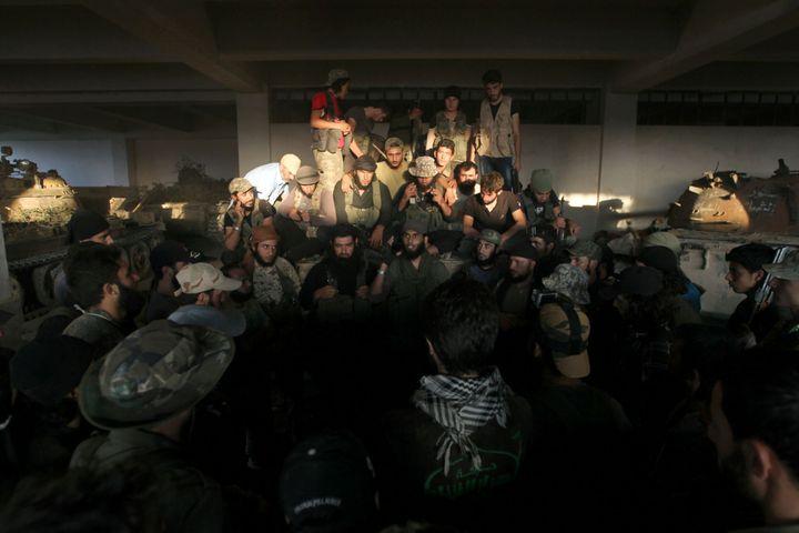 Des combattants rebelles se rassemblent dans l'école d'artillerie nouvellement prise, le 6 août 2016. (Ammar Abdullah / Reuters)